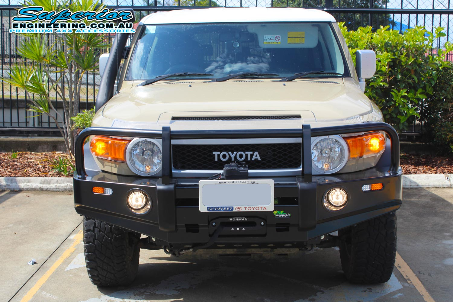 Front view of a brown Toyota FJ Cruiser fitted with a Ironman 4x4 Black Commercial Bullbar, Monster Winch and TJM Snorkel