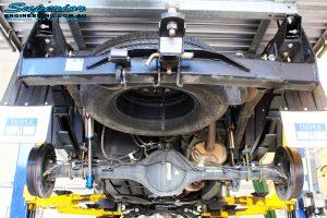 Mid rear underbody shot of the fitted Piggy Back Remote Reservoir Shocks, U-Bolt Kit and Rear Leaf Springs