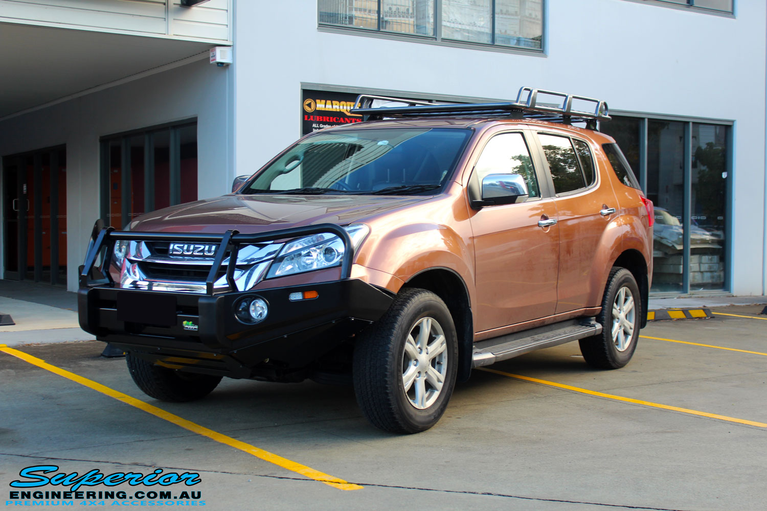 Left front side view of a Gold Isuzu MU-X Wagon after fitment of a Ironman 4x4 Roof Rack & Black Deluxe Bull Bar