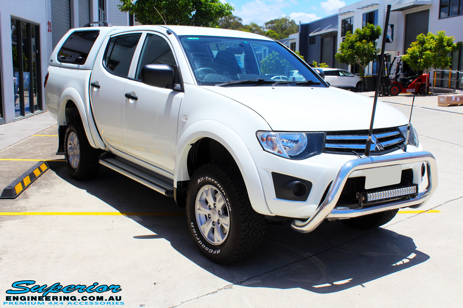 """Right front side view of a Mitsubishi MN Triton in White after fitment of a Superior Nitro Gas 2"""" Inch Lift Kit"""