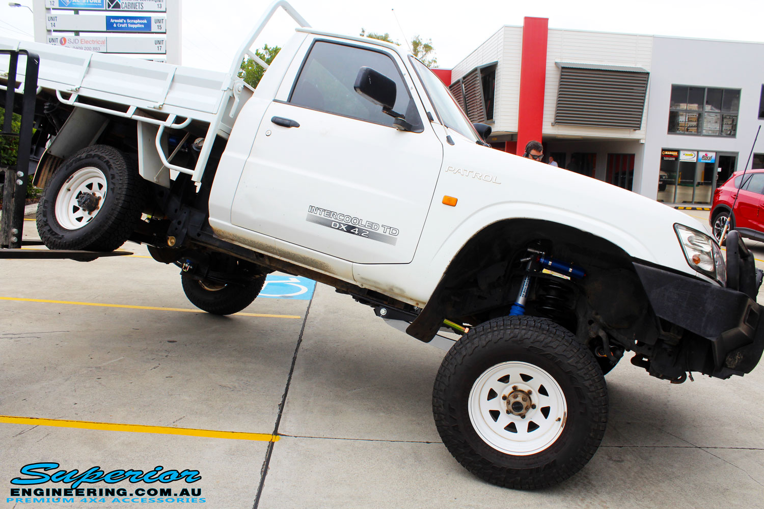 Right side view of this Nissan GU Patrol Ute being flexed from the rear left tyre after fitment of a Superior 4-5 Inch Lift Kit with Superior Remote Reservoir Shocks & Superior Hybrid 5 Link Radius Arms