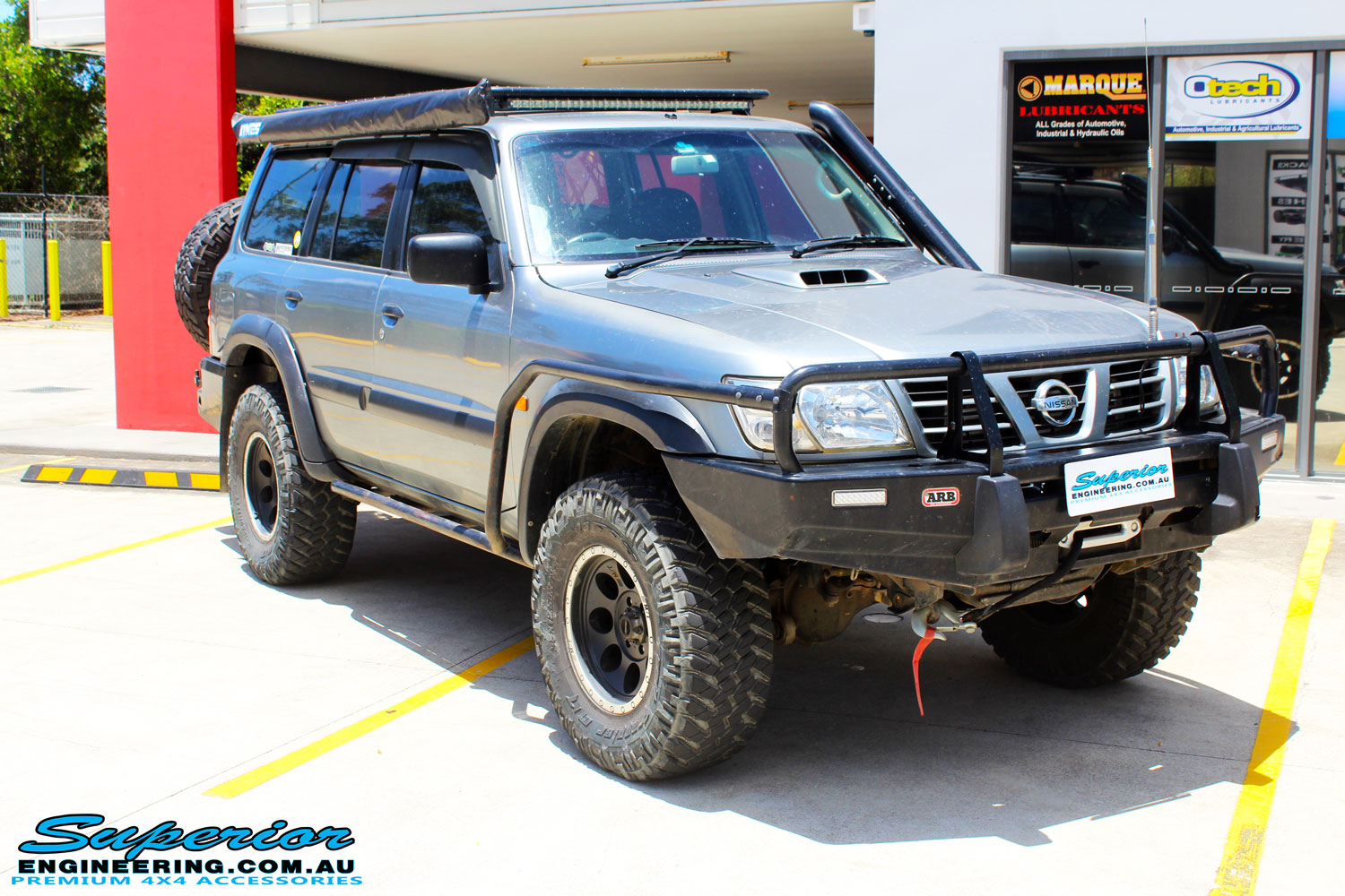 Right front side view of a Nissan GU Patrol Wagon in Silver On The Hoist @ Superior Engineering Deception Bay Showroom getting fitted with a Superior Coil Tower Brace Kit