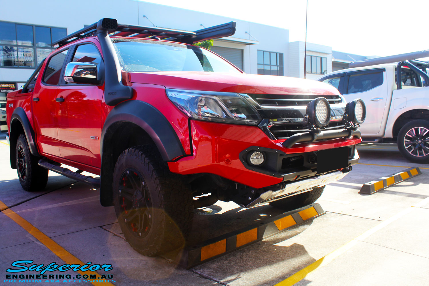 Front right corner view of a Holden RG Colorado Dual Cab in Red after fitment of a Colour Coded Rhino 4x4 Evolution 3D Winch Bar with Warn Winch