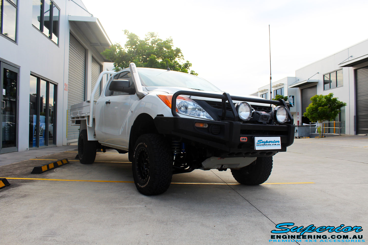 "Right front side view of a Mazda BT50 in White after fitment of a Superior 3"" Inch Remote Reservoir Lift Kit with Nitto Terra Grappler Tyres + ROH Black Steel Wheels"