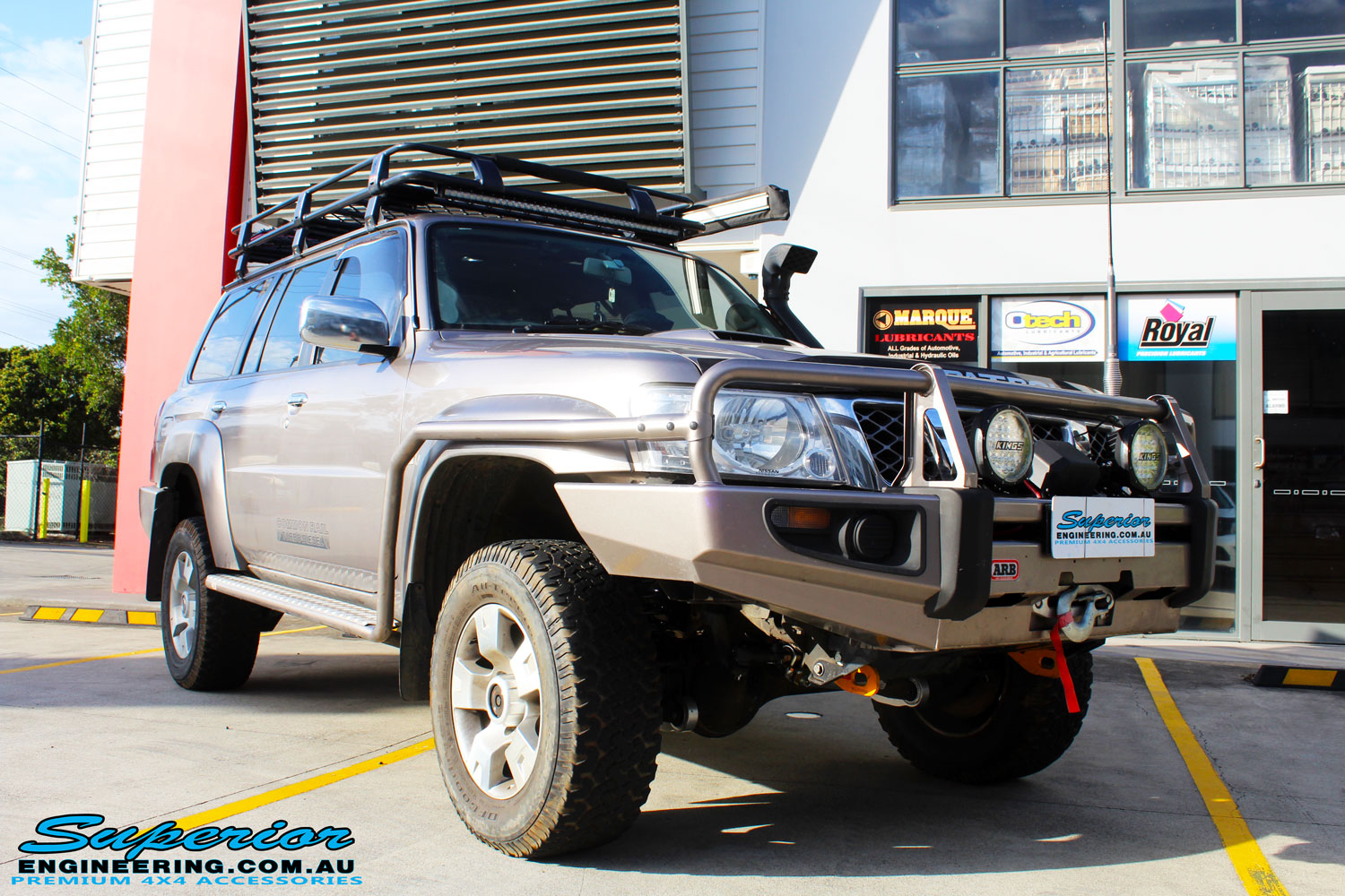 """Front right side view of a Brown Nissan GU Patrol Wagon after fitment of a Superior Nitro Gas 2"""" Inch Lift Kit, Front & Rear Adjustable Panhard Rods, Coil Tower Brace Kit, Superior Hybrid Radius Arms, Superior Comp Spec Tie Rod and Superior Solid Bar Comp Spec Adjustable Drag Link"""